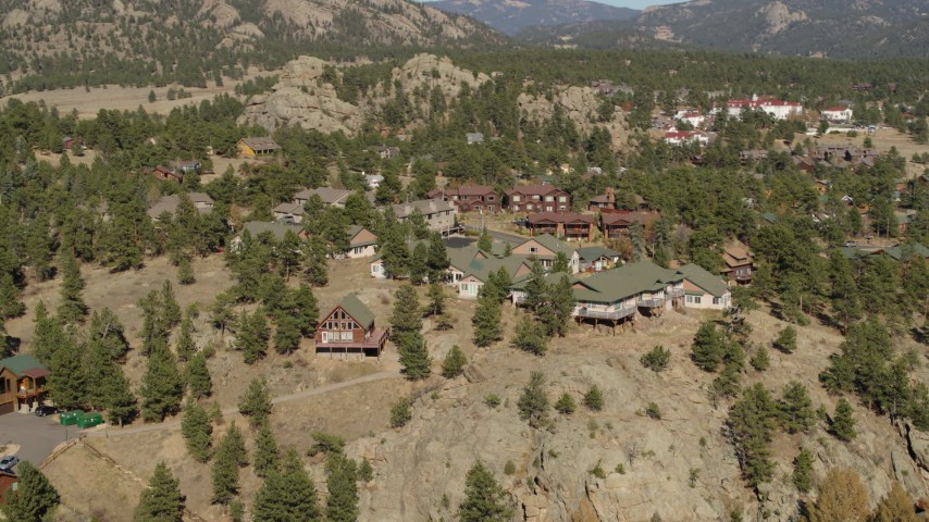5.7K aerial video flying away from rural hillside homes near rugged mountains in Estes Park, Colorado Aerial Stock Footage | DX0001_002006