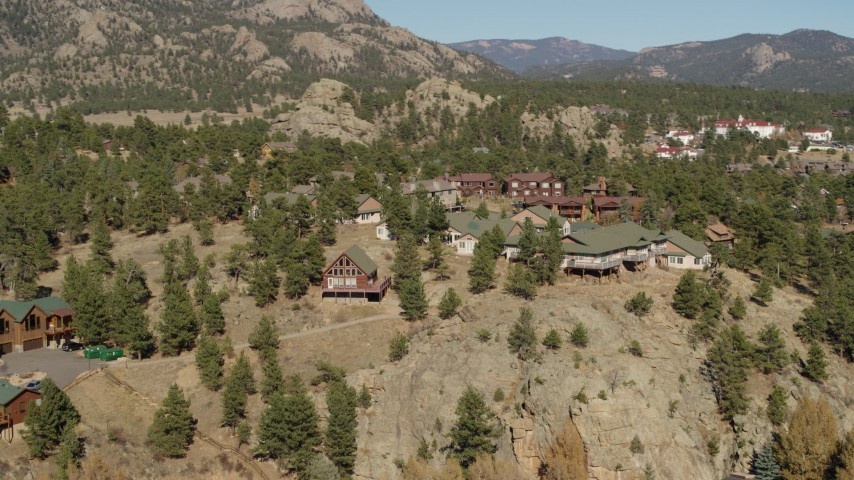 5.7K aerial video of rural hillside homes near rugged mountains during descent in Estes Park, Colorado Aerial Stock Footage | DX0001_002007