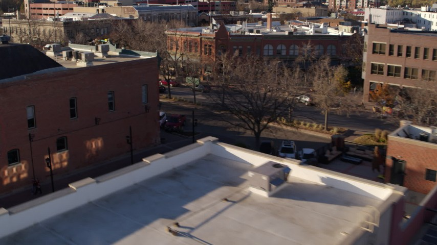 5.7K stock footage aerial video of passing brick office buildings and street level shop in Fort Collins, Colorado Aerial Stock Footage | DX0001_002042