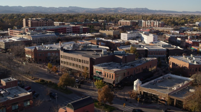 5.7K stock footage aerial video of passing brick office buildings and street level shops in Fort Collins, Colorado Aerial Stock Footage | DX0001_002045