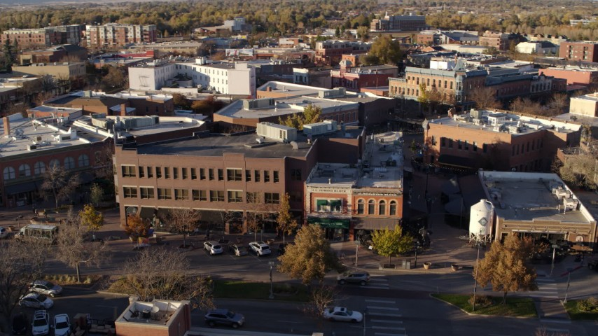 5.7K stock footage aerial video passing a shop with green awning and brick office building in Fort Collins, Colorado Aerial Stock Footage | DX0001_002058