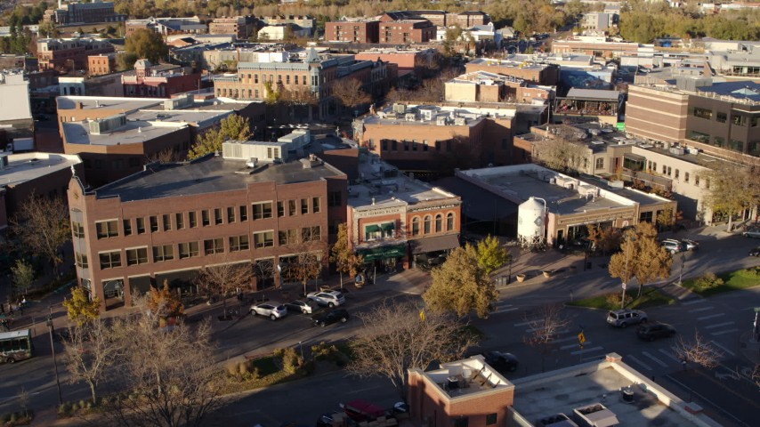 5.7K stock footage aerial video people and cars passing a shop with green awning and brick office building in Fort Collins, Colorado Aerial Stock Footage | DX0001_002059