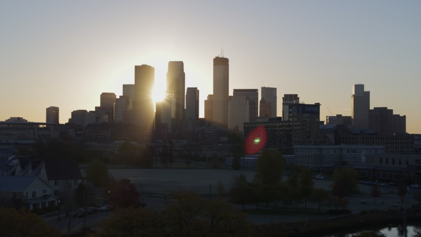 5.7K stock footage aerial video of the rising sun behind the city skyline seen during ascent in Downtown Minneapolis, Minnesota Aerial Stock Footage | DX0001_002080