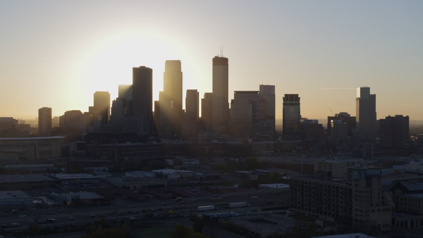 5.7K stock footage aerial video flying by the rising sun behind the city skyline in Downtown Minneapolis, Minnesota Aerial Stock Footage | DX0001_002081