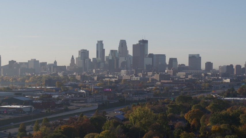 5.7K stock footage aerial video ascend from behind trees to reveal skyline at sunrise in Downtown Minneapolis, Minnesota Aerial Stock Footage | DX0001_002090