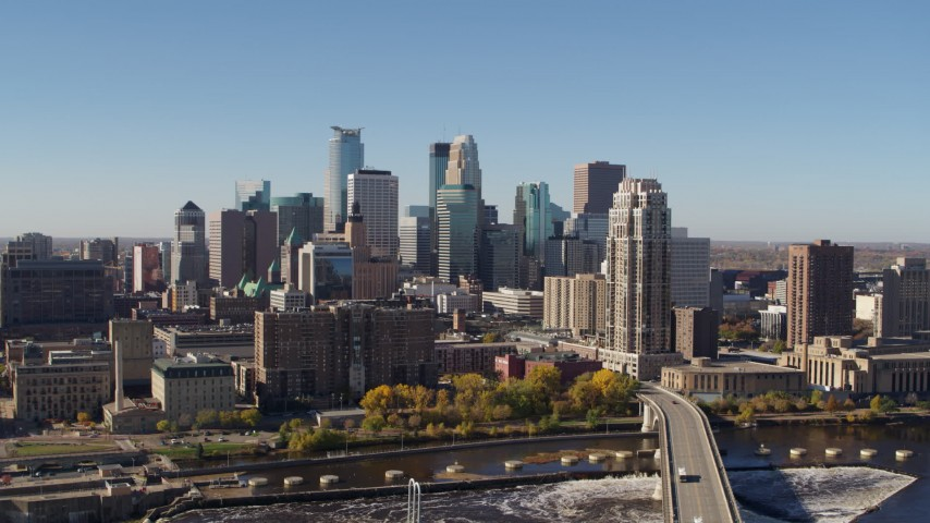 5.7K stock footage aerial video slowly flying by the skyline, seen from a bridge spanning the river in Downtown Minneapolis, Minnesota Aerial Stock Footage | DX0001_002136