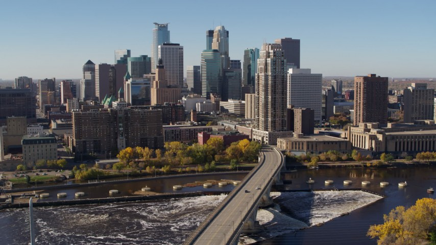 5.7K stock footage aerial video slowly passing by the skyline, seen from a bridge spanning the river in Downtown Minneapolis, Minnesota Aerial Stock Footage | DX0001_002137