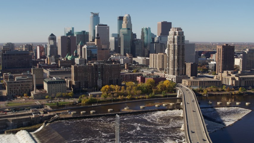 5.7K stock footage aerial video passing by the skyline, seen from a bridge spanning the river in Downtown Minneapolis, Minnesota Aerial Stock Footage | DX0001_002138