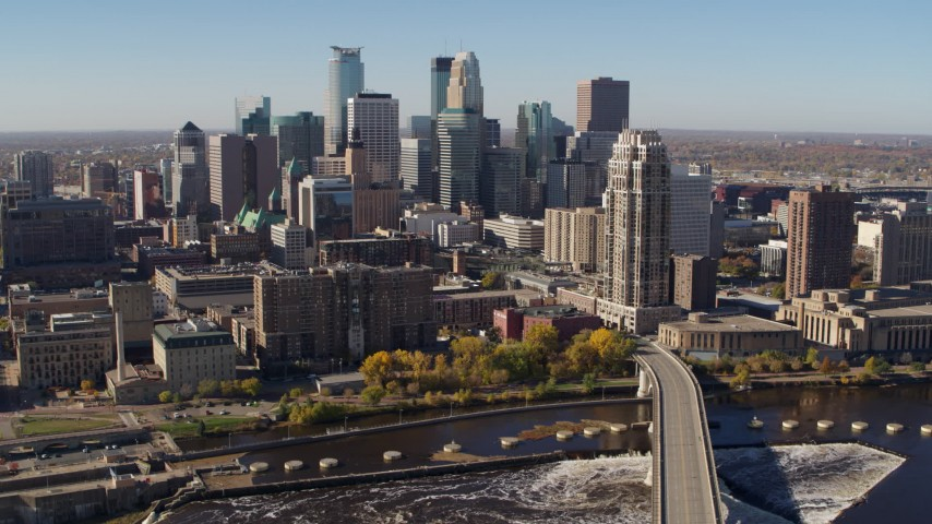 5.7K stock footage aerial video flying by the skyline, seen from a bridge spanning the river in Downtown Minneapolis, Minnesota Aerial Stock Footage DX0001_002139 | Axiom Images
