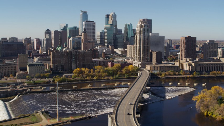 5.7K stock footage aerial video descend by the skyline, seen from a bridge spanning the river in Downtown Minneapolis, Minnesota Aerial Stock Footage | DX0001_002140