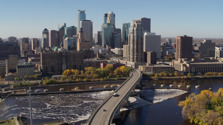 5.7K stock footage aerial video descend near a bridge spanning the river with a view of the skyline, Downtown Minneapolis, Minnesota Aerial Stock Footage | DX0001_002142