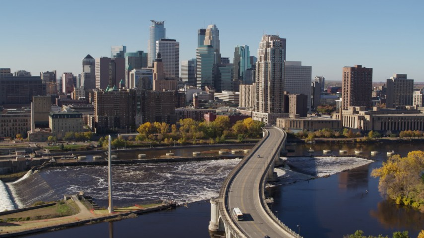 5.7K stock footage aerial video flying by a bridge spanning the river with a view of the skyline, Downtown Minneapolis, Minnesota Aerial Stock Footage | DX0001_002143