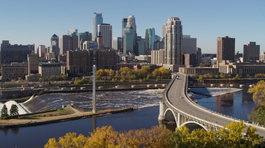 5.7K stock footage aerial video flying by a bridge spanning the river and ascend, with a view of the skyline, Downtown Minneapolis, Minnesota Aerial Stock Footage | DX0001_002145