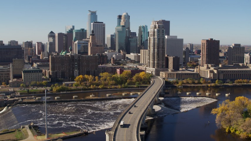 5.7K stock footage aerial video descend by a bridge spanning the river for stationary view of the skyline, Downtown Minneapolis, Minnesota Aerial Stock Footage | DX0001_002146