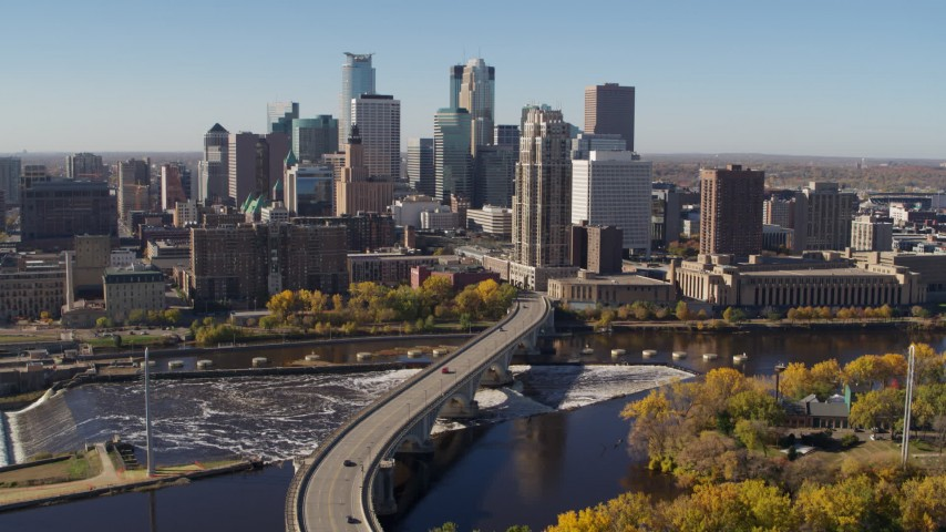 5.7K stock footage aerial video ascend by a bridge spanning the river while flying away from the skyline, Downtown Minneapolis, Minnesota Aerial Stock Footage | DX0001_002147