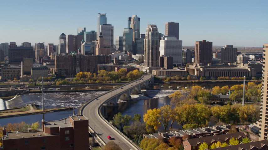 5.7K stock footage aerial video descend near a bridge spanning the river with view of the skyline, Downtown Minneapolis, Minnesota Aerial Stock Footage | DX0001_002148