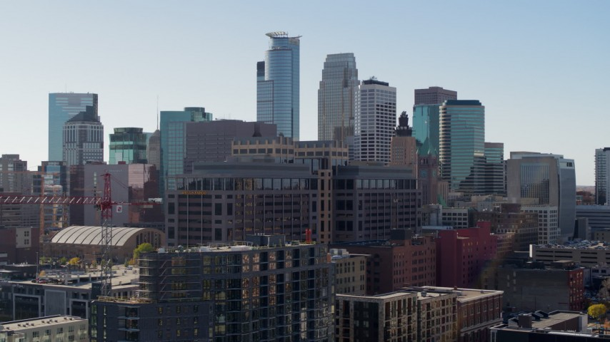 5.7K stock footage aerial video flying by office building with view of the city's skyline during ascent, Downtown Minneapolis, Minnesota Aerial Stock Footage | DX0001_002157