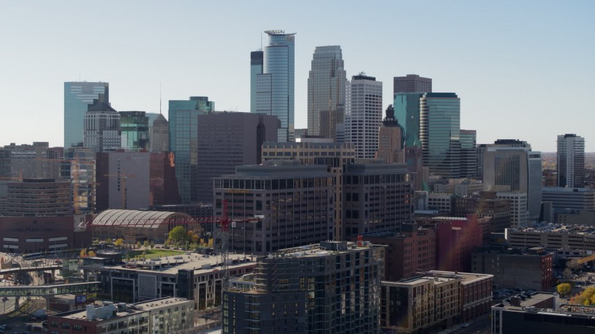 5.7K stock footage aerial video descend near office building and city's skyline before flyby, Downtown Minneapolis, Minnesota Aerial Stock Footage | DX0001_002163