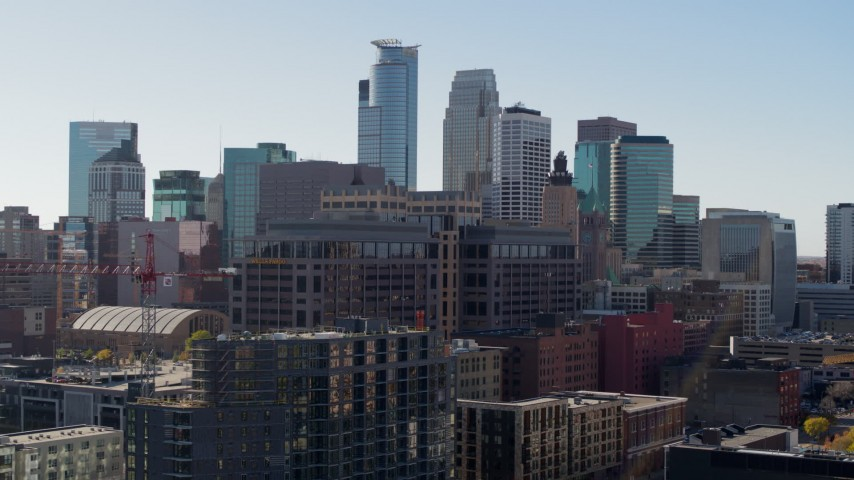 5.7K stock footage aerial video descend by office building and construction, city's skyline in background, Downtown Minneapolis, Minnesota Aerial Stock Footage | DX0001_002164