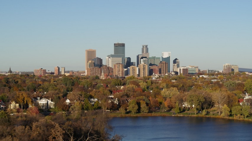 5.7K stock footage aerial video of the city's skyline seen while flying by lakefront houses, Downtown Minneapolis, Minnesota Aerial Stock Footage | DX0001_002191