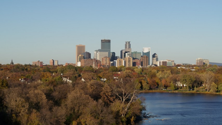5.7K stock footage aerial video of the city's skyline seen while passing by lakefront houses, Downtown Minneapolis, Minnesota Aerial Stock Footage | DX0001_002192