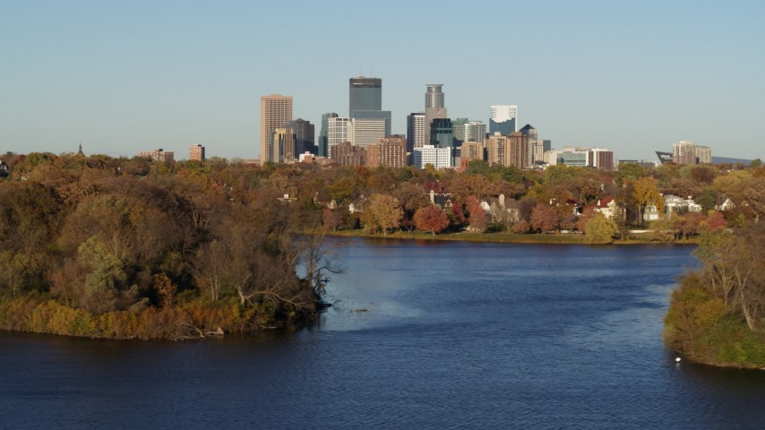 5.7K stock footage aerial video of the city's skyline seen while passing by lakeside houses, Downtown Minneapolis, Minnesota Aerial Stock Footage | DX0001_002193