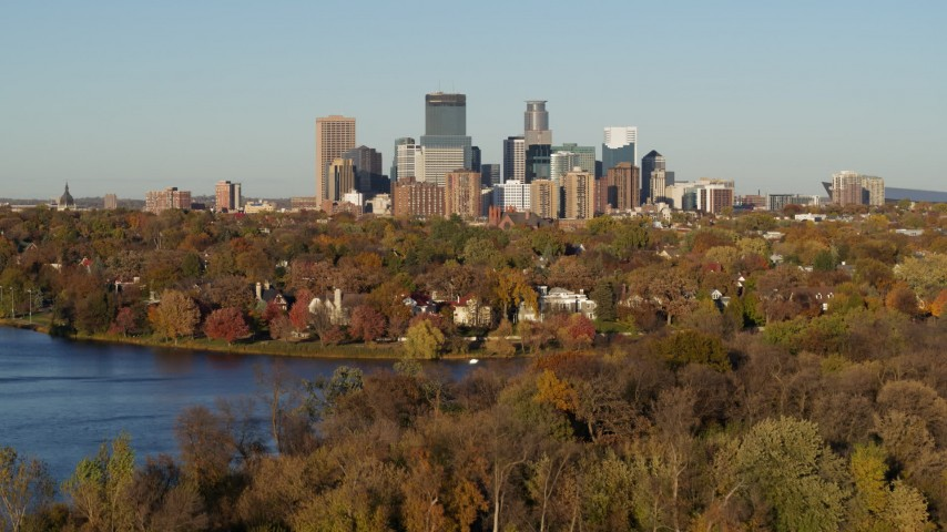 5.7K stock footage aerial video descend toward Lake of the Isles with a view of the downtown skyline, Downtown Minneapolis, Minnesota Aerial Stock Footage | DX0001_002199