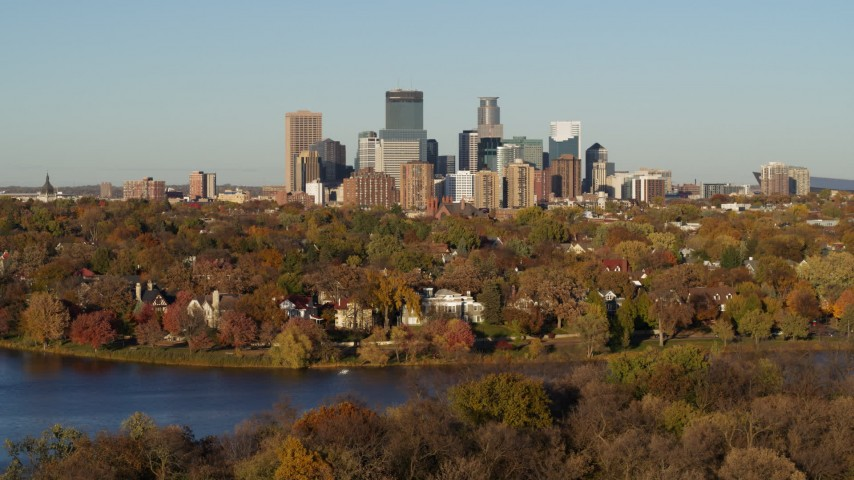 5.7K stock footage aerial video ascend from Lake of the Isles to reveal homes and city skyline, Downtown Minneapolis, Minnesota Aerial Stock Footage | DX0001_002204