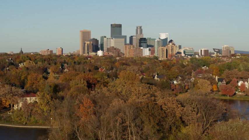 5.7K stock footage aerial video of reverse view of the city skyline, seen from Lake of the Isles, Downtown Minneapolis, Minnesota Aerial Stock Footage | DX0001_002206