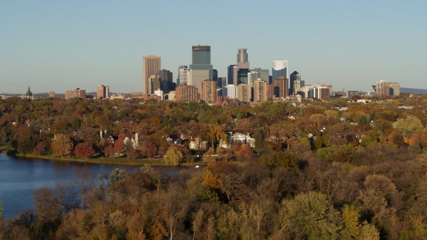 5.7K stock footage aerial video ascend from Lake of the Isles for wide view of the skyline of Downtown Minneapolis, Minnesota Aerial Stock Footage | DX0001_002207
