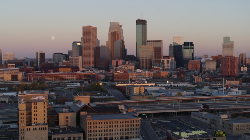 5.7K stock footage aerial video reverse view of the city's skyline at sunset with moon in the sky, Downtown Minneapolis, Minnesota Aerial Stock Footage | DX0001_002237