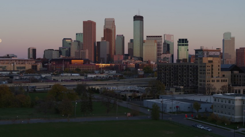 5.7K stock footage aerial video reverse view of city's skyline at sunset, seen from park, Downtown Minneapolis, Minnesota Aerial Stock Footage | DX0001_002242