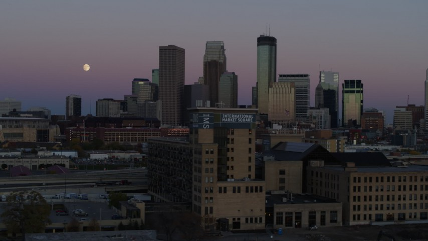 5.7K stock footage aerial video flying by the city's downtown skyline at twilight, reveal moon and market, Downtown Minneapolis, Minnesota Aerial Stock Footage | DX0001_002251