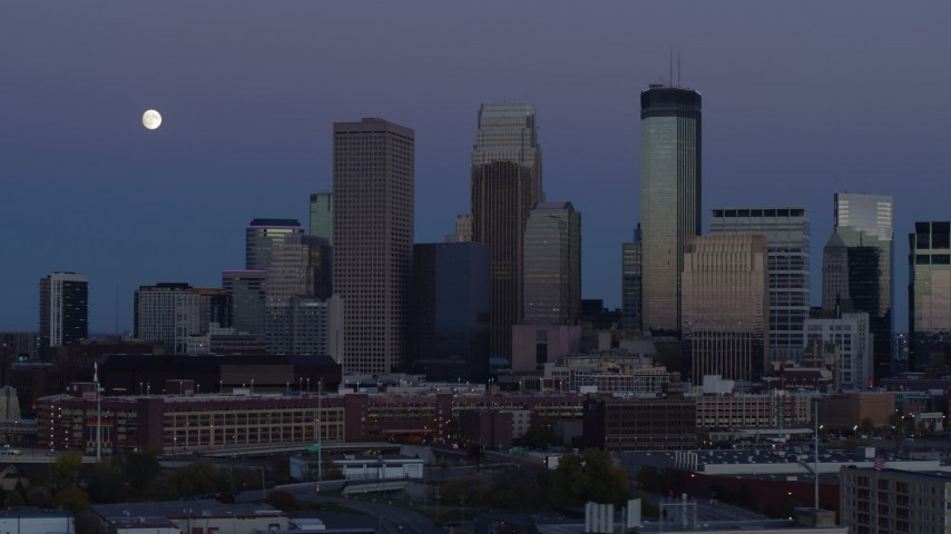 5.7K stock footage aerial video of flying by the city's skyline at twilight with moon in the sky, Downtown Minneapolis, Minnesota Aerial Stock Footage | DX0001_002262