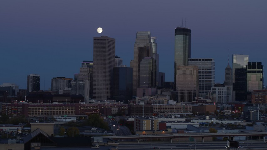 5.7K stock footage aerial video of passing by the city's skyline at twilight with moon in the sky, Downtown Minneapolis, Minnesota Aerial Stock Footage | DX0001_002263