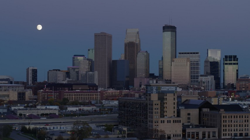 5.7K stock footage aerial video passing market with the city's skyline and moon in background at twilight, Downtown Minneapolis, Minnesota Aerial Stock Footage | DX0001_002264