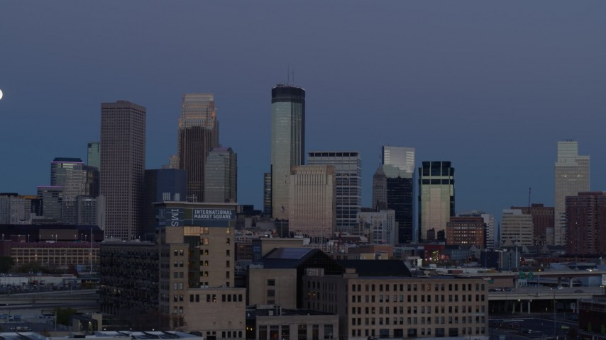 5.7K stock footage aerial video flyby the city's skyline with the moon in the sky at twilight, reveal market, Downtown Minneapolis, Minnesota Aerial Stock Footage | DX0001_002266
