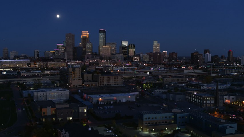 5.7K stock footage aerial video flying by the moon above city's downtown skyline at twilight, Downtown Minneapolis, Minnesota Aerial Stock Footage | DX0001_002281