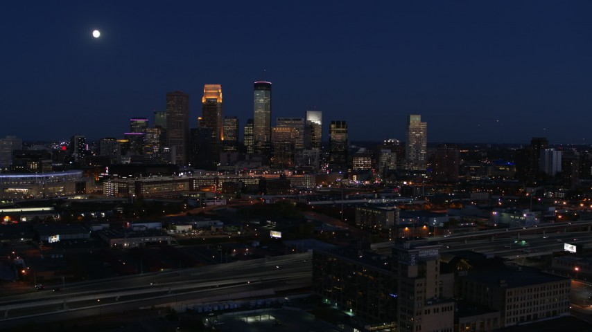 5.7K stock footage aerial video descend with view of moon above city's skyline at twilight, Downtown Minneapolis, Minnesota Aerial Stock Footage | DX0001_002286