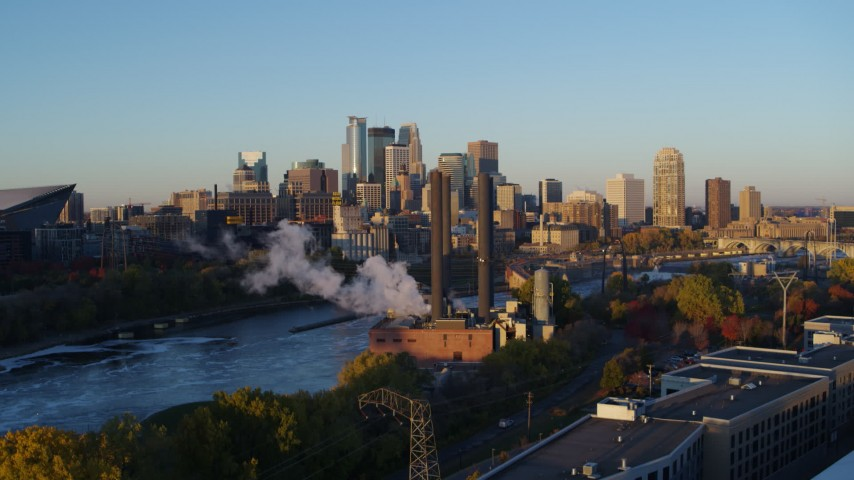 5.7K stock footage aerial video ascend to reveal power plant, and the city skyline across the river at sunrise, Downtown Minneapolis, Minnesota Aerial Stock Footage | DX0001_002289