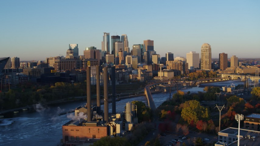 5.7K stock footage aerial video flyby power plant and bridge with the city skyline across the river at sunrise, Downtown Minneapolis, Minnesota Aerial Stock Footage | DX0001_002290