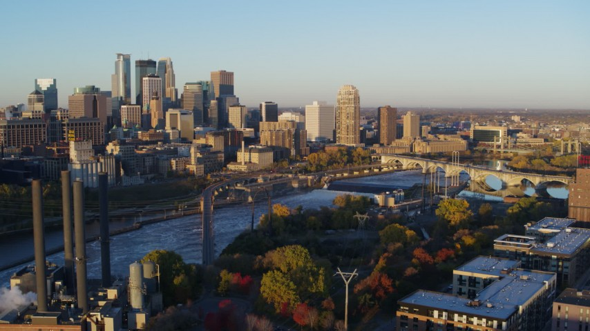 5.7K stock footage aerial video of flying by bridge and Mississippi River at sunrise, with view of skyline, Downtown Minneapolis, Minnesota Aerial Stock Footage | DX0001_002296