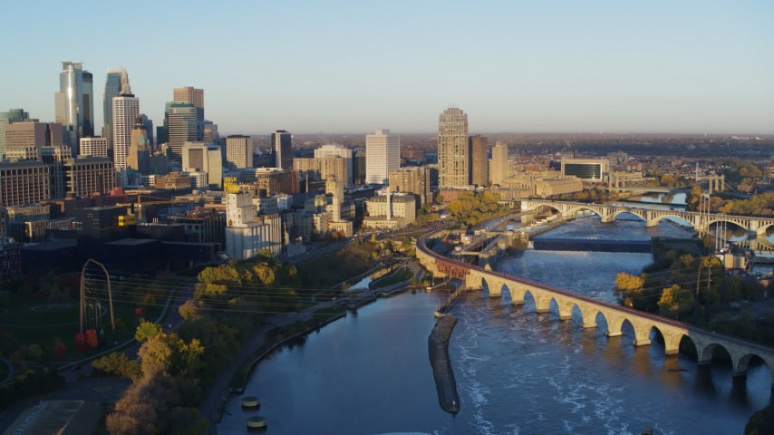 5.7K stock footage aerial video passing bridge and river to reveal power plant, with view of skyline at sunrise, Downtown Minneapolis, Minnesota Aerial Stock Footage DX0001_002300 | Axiom Images