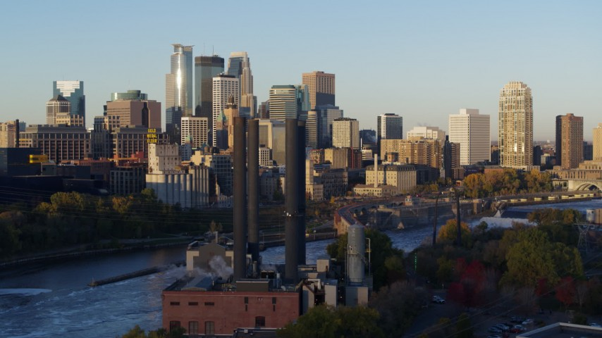 5.7K stock footage aerial video descend past power plant with view of skyline at sunrise, Downtown Minneapolis, Minnesota Aerial Stock Footage | DX0001_002302