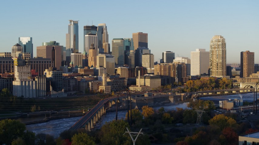 5.7K stock footage aerial video of a view of skyline across the Mississippi River at sunrise, Downtown Minneapolis, Minnesota Aerial Stock Footage DX0001_002303 | Axiom Images