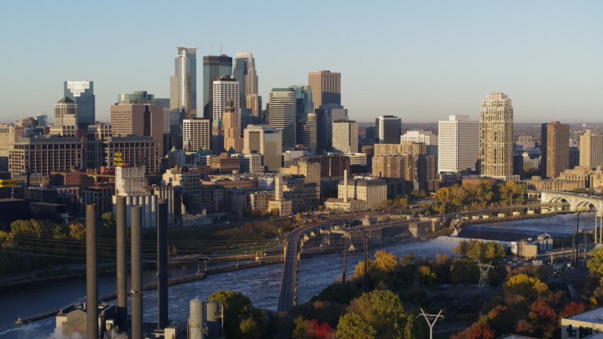 5.7K stock footage aerial video of a view of the city skyline across the river at sunrise during descent, Downtown Minneapolis, Minnesota Aerial Stock Footage | DX0001_002305