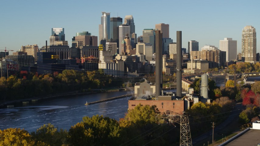 5.7K stock footage aerial video descend by riverfront power plant at sunrise, with skyline in background, Downtown Minneapolis, Minnesota Aerial Stock Footage | DX0001_002327