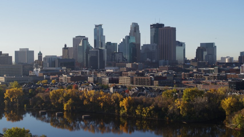 5.7K stock footage aerial video of flying by the skyline seen from a park by the river, Downtown Minneapolis, Minnesota Aerial Stock Footage DX0001_002329 | Axiom Images