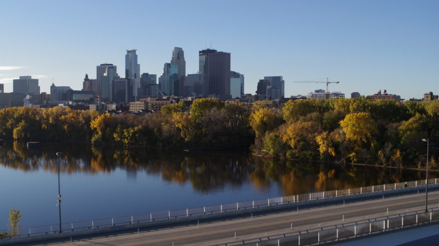 5.7K stock footage aerial video reverse view of city's skyline, revealing bridge and river, Downtown Minneapolis, Minnesota Aerial Stock Footage | DX0001_002336