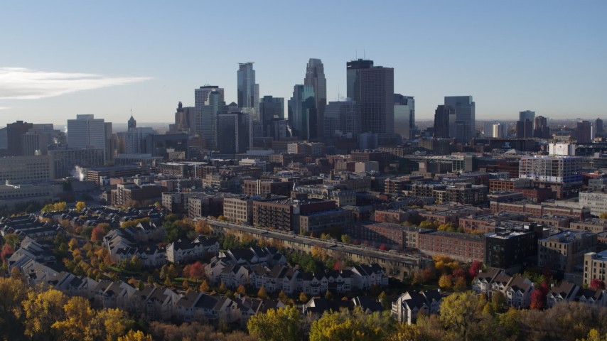 5.7K stock footage aerial video descend toward trees and focus on skyline of Downtown Minneapolis, Minnesota Aerial Stock Footage | DX0001_002340
